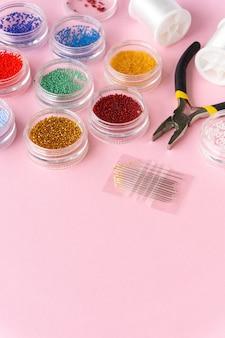 Articoli per la creatività. perline, lenza e tronchesi su sfondo rosa, copyspace.