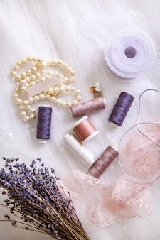 Articoli per sartoria, rocchetti di filo, aghi, nastri, pizzi, bottoni e una collana di perle vista dall'alto