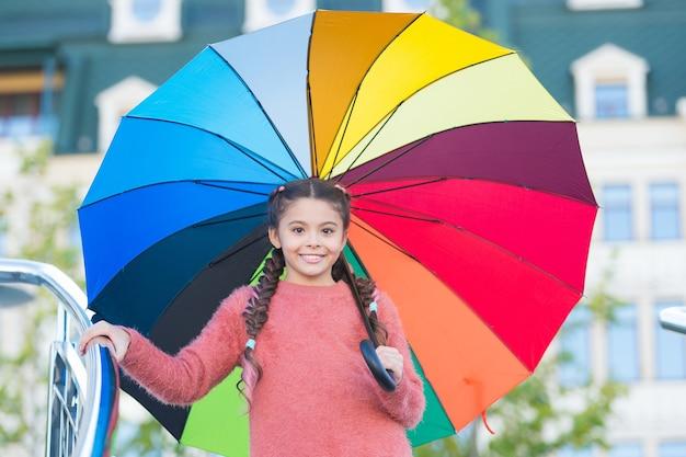 È autunno. ragazza felice il giorno d'autunno. piccola ragazza sorridenti sotto l'ombrello color arcobaleno. bambina con accessorio di moda. tendenze moda per l'autunno. senza la pioggia non ci sarebbe l'arcobaleno.