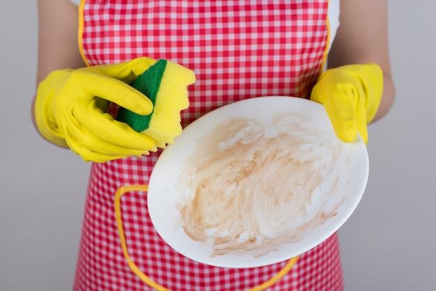 Non è facile usare solo sapone liquido per rimuovere tutto il grasso e l'appiccicosità dal concetto di piastra bianca. foto ravvicinata ritagliata di braccia che tengono una ciotola vuota su sfondo grigio isolato