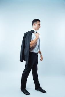 È caldo. piacevole simpatico uomo allegro che tiene la sua giacca e cammina su sfondo blu mentre si sente caldo
