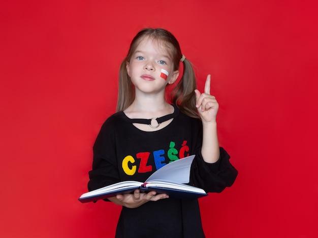 Piccola ragazza che tiene un taccuino o un libro in mano, concetto di pubblicità per imparare il polacco