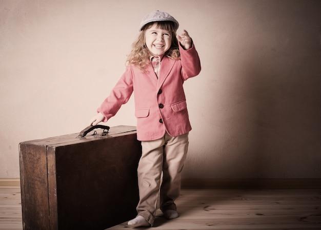 Piccola ragazza con la valigia al coperto