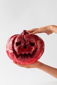 Jack lantern halloween rosso nella mano di un bambino su uno sfondo bianco felice halloween copia spazio