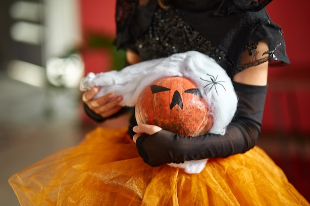 Jack o lantern, zucca di halloween nella protezione medica maschera nera nelle mani della ragazza durante la celebrazione di halloween a casa covid19 pandemia di coronavirus, copia spazio