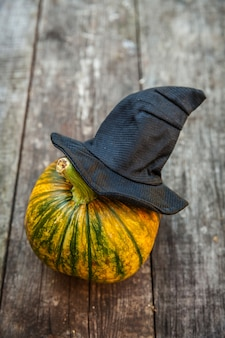 Zucca di halloween di jack o lantern con il cappello nero della strega su fondo di legno. concetto di festa di halloween. saluto delle festività natalizie, scherzetto spettrale.