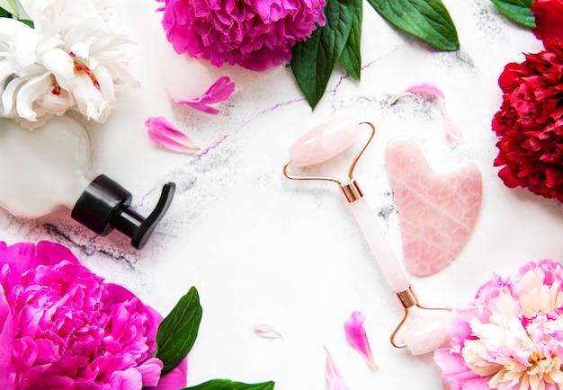 Rullo facciale in giada per terapia di massaggio del viso di bellezza, oli da massaggio e peonie rosa.