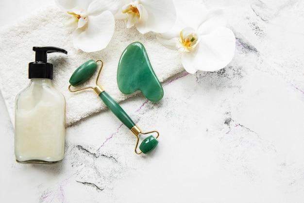 Rullo facciale in giada per massoterapia estetica del viso con asciugamano e fiori di orchidea.