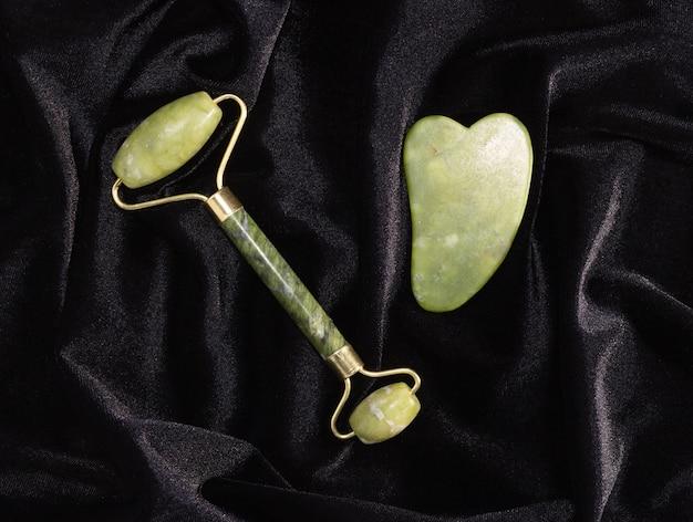 Jade gua sha raschietto, massaggiatore facciale a rullo su sfondo nero