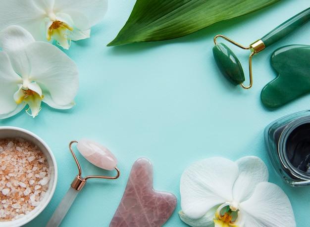 Rulli di giada per massaggio viso su sfondo verde pastello