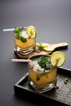 Jal-jeera o jaljira è una bevanda indiana preparata mescolando la polvere di cumino in acqua e servita fredda con boondi, menta e fetta di limone. servito su sfondo lunatico. messa a fuoco selettiva