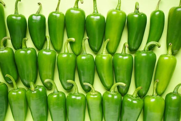Jalapeno peperoni verdi, su uno sfondo verde. disposizione piatta.