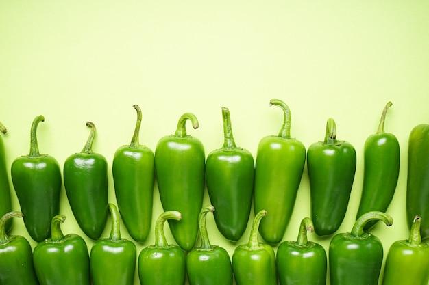 Peperoni jalapeno, su sfondo verde chiaro, spazio per il testo. disposizione piatta.