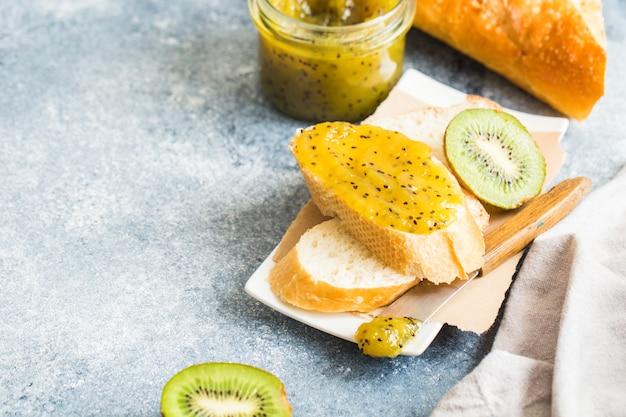 Marmellata o marmellata a base di kiwi su pane fresco. colazione, pane tostato con marmellata su uno sfondo grigio
