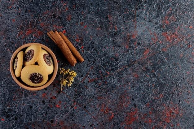 Biscotto alla marmellata in una ciotola di argilla con bastoncini di cannella e fiore di mimosa.