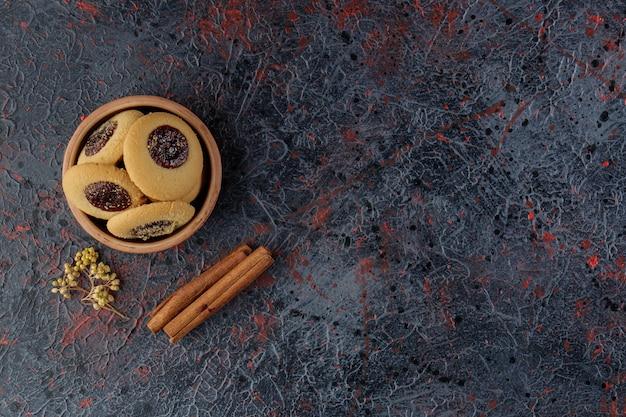 Biscotto alla marmellata in una ciotola di argilla con bastoncini di cannella e fiore di mimosa