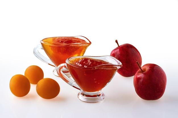 Marmellate di prugne e mele su sfondo bianco