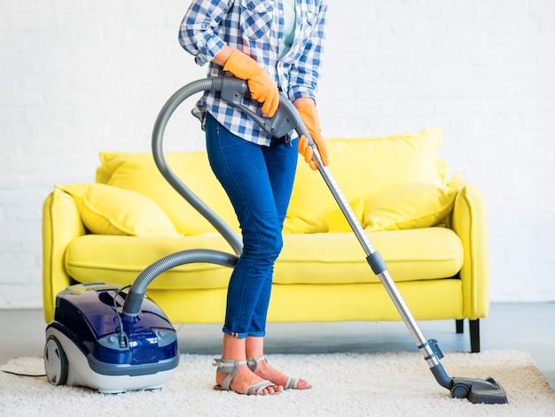 Bidello pulizia tappeto con aspirapolvere di fronte al divano giallo