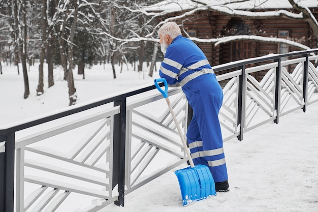 Portiere che si appoggia sui corrimani e che osserva in avanti in inverno