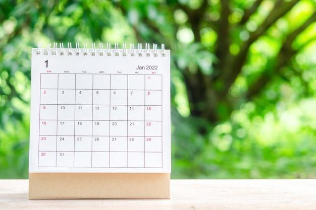 Mese di gennaio, scrivania del calendario 2022 per l'organizzatore per la pianificazione e il promemoria sul tavolo di legno con sfondo verde della natura.
