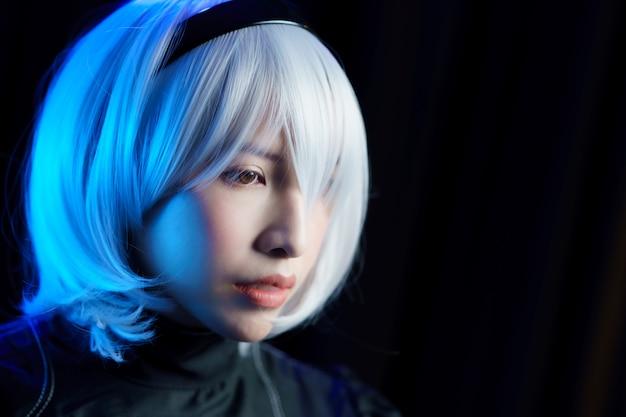 Cosplay di anime giapponesi. ritratto di donna in abito nero con i capelli bianchi.