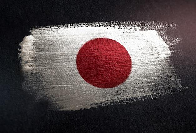 Bandiera del giappone fatta di vernice pennello metallico sulla parete scura del grunge