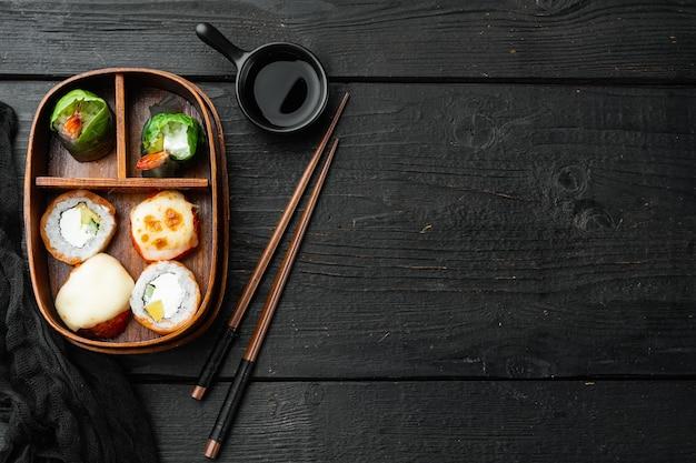 Lunch box bento giapponese con set di bacchette, sul tavolo di legno nero