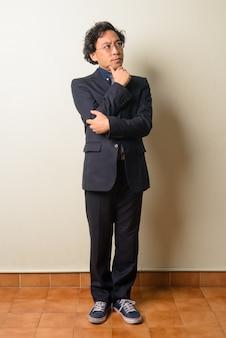 Uomo d'affari giapponese in vestito con capelli ricci al chiuso