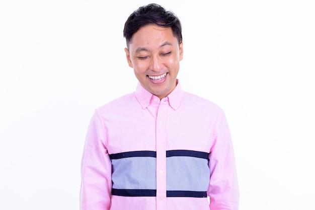 Uomo d'affari giapponese con camicia rosa isolata contro il muro bianco