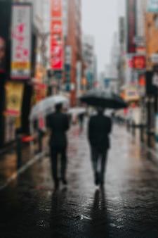 Uomini d'affari giapponesi che camminano con gli ombrelli a tokyo
