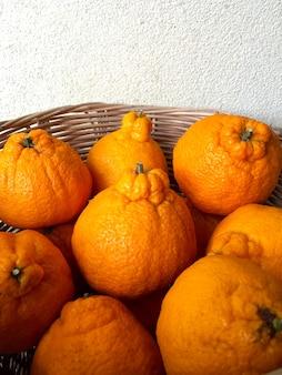 Nome giapponese degli agrumi arancioni dekopon nel cestino.