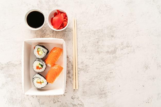 Concetto di cucina giapponese. set di sushi con salsa di soia, zenzero e bacchette su sfondo bianco marmo