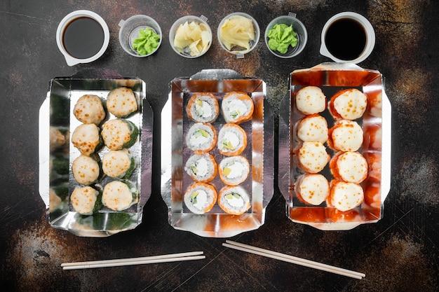 Concetto di cibo giapponese. catering, vari tipi di rotoli di sushi philadelphia e set di rotoli di gamberi al forno, su vecchio sfondo rustico scuro, vista dall'alto piatta