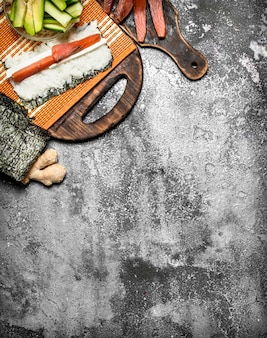 Cibo giapponese. cucinare involtini tradizionali con pesce fresco. su fondo rustico. Foto Premium