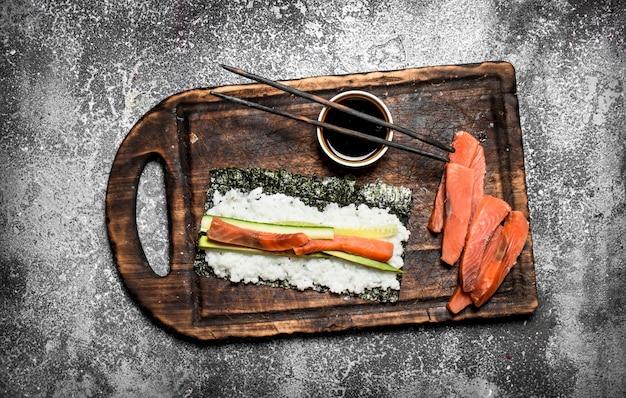 Cibo giapponese. cucinare involtini tradizionali con pesce fresco. sulla tavola rustica.