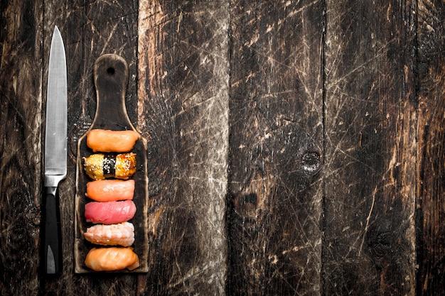 Cibo giapponese. sushi fresco di anguilla, gamberetti e tonno su una tavola di legno. sul vecchio sfondo di legno.