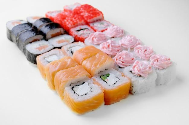 Consegna del ristorante di cibo giapponese, set di sushi. sushi unagi, tempura rotoli california con salmone, gamberetti, tonno, caviale e formaggio isolato.