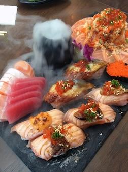 Cibo giapponese, set di sashimi, gruppo di sushi con fumo sul tavolo.