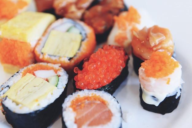 Rotolo di sushi di cibo giapponese con uovo di tobiko caviale rosso salsa di panna nori nel ristorante sashimi menu di sushi set cucina giapponese ingredienti freschi mescolare vari tipi sul piatto bianco