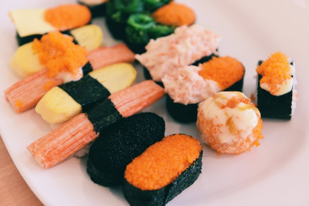 Rotolo di sushi con cibo giapponese con uovo di tobiko caviale rosso salsa di panna alga nori nel ristorante set di menu di sushi di sashimi cucina giapponese ingredienti freschi mescolano vari tipi