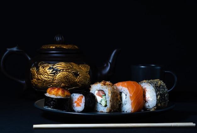 Cucina giapponese set di panini su un piatto nero e una teiera con un drago d'oro sullo sfondo