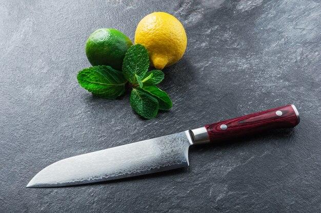 Il coltello giapponese in acciaio damasco giace su un tavolo vicino alla menta e agli agrumi. vista dall'alto