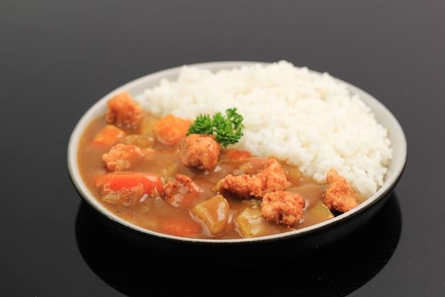 Curry giapponese o coreano con riso - stile alimentare giapponese. servito su piatto in ceramica isolato tavolo nero con patate, popcorn di pollo croccante e dadi di carota, copia spazio per il testo
