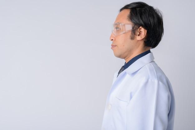 Uomo giapponese medico indossando occhiali protettivi contro uno sfondo bianco