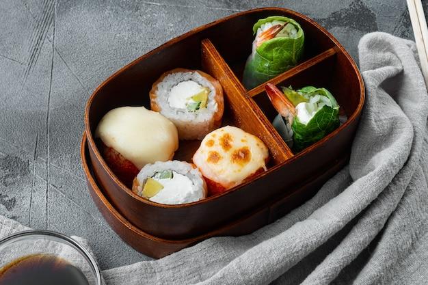 Pasto giapponese in una scatola bento con set di sushi roll eice avocado salmone, su pietra grigia