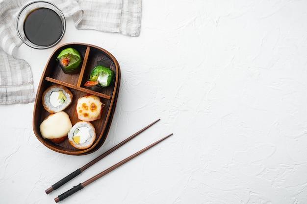 Pasto giapponese in una scatola bento con set di sushi roll eice avocado salmone, su pietra bianca