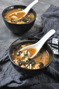 Zuppa di miso giapponese con tonno fresco, alghe secche, tofu, funghi secchi shiitake in una ciotola di legno sullo sfondo in legno