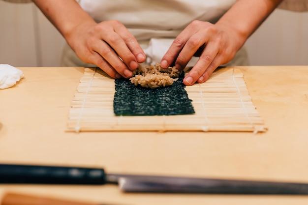 Giapponese omakase chef mano arrotolando un tuna nori hand roll ordinatamente per mano