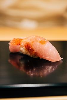 Omakase giapponese in stile edo: close up sushi otoro (tonni grassi) servito su piastra nera lucida. pasto di lusso tradizionale giapponese.