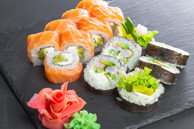 Ristorante giapponese, rotolo di sushi su lastra di ardesia nera.